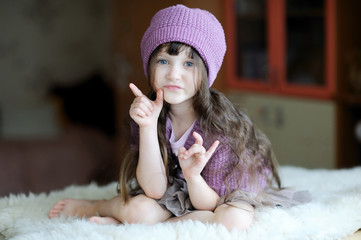 Beauty toddler girl in purple hat sitting on white fur