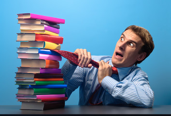man at the table looking with fear at a stack of colored books