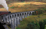 Steam train travelling across the Glenfinnan Viaduct, Scotland poster