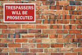 'Trespassers' will be prosecuted' sign, against brick wall. Spac