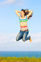 Beautiful young woman jumping up in the air smiling