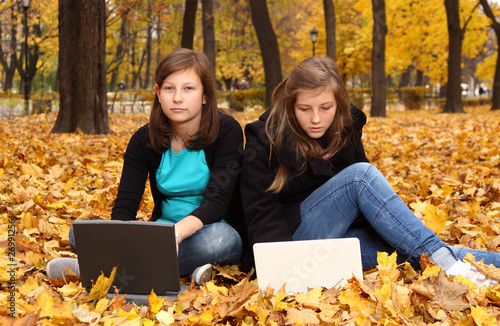 teenagers with a computer in the autumn park