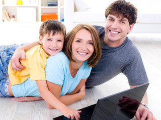 Family with son on the floor with laptop
