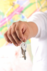 Man holding a house key with shallow DOF, focus on key.