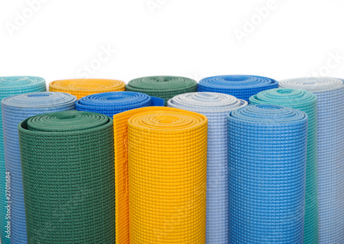 many colorfull yoga mats as a background. isolated on white back