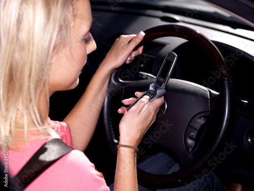 Young Woman Driving Texting on Mobile Telephone. Model Released