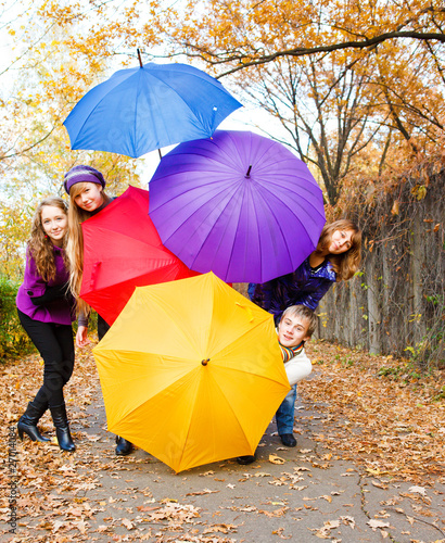 Friends hiding behind umbrellas