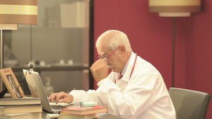 Senior doctor working on laptop; HD: Photo JPEG, dolly.