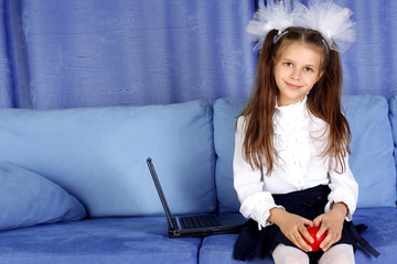 schoolgirl with laptop and red apple in sofa