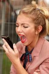 Angry Young Woman Using Mobile Telephone. Model Released