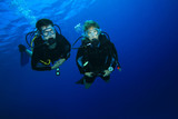 Couple scuba diving on a coral reef poster