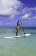 teenage girl in bikini on a paddle board in hawaii