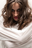 Young insane woman with straitjacket looking at camera close-up