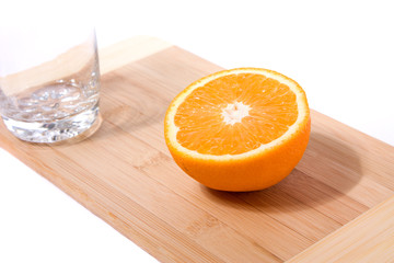 orange and glass on cutting board on white background