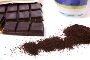 dark chocolate, ground coffee and mug over white