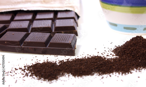 dark chocolate, ground coffee and mug over white