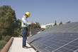 Maintenance worker stands with solar array on rooftop, Los Angeles, California