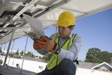 Maintenance worker refers to notes under solar panel in Los Angeles, California