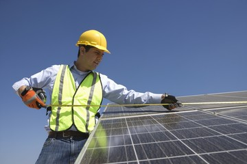 Maintenance worker measures solar cells in Los Angeles, California