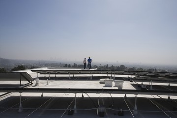 Maintenance workers stand with solar array on rooftop in Los Angeles, California