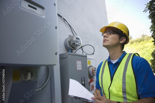 Maintenance worker reads meter of solar generation unit in Los Angeles, California