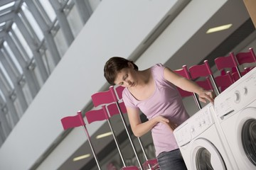 Young woman measures washing machine in shopping mall, Voronezh