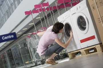 Young woman looks inside tub of washing machine in shopping mall, Voronezh