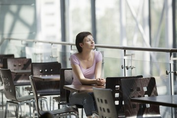Young woman sits in food hall of shopping mall, Voronezh