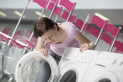 Young woman chooses washing machine in shopping mall, Voronezh
