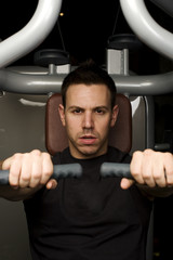 Young man working out on exercise machine