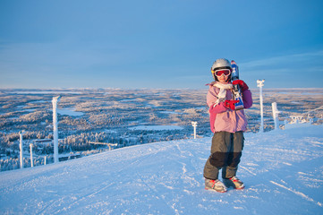 Little girl-skier on the hill watching the sunrise at a ski reso