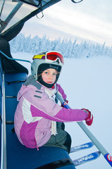 Little girl-skier on the ski lift watching the sunrise at a ski