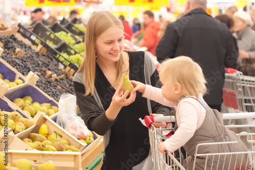 young mother and toddler girl shopping pear in supermarket