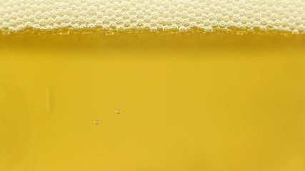 Golden cold beer being poured into glass, close-up