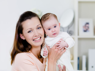 Happy woman with newborn child at home