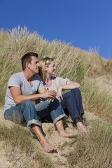 Romantic Man and Woman Couple Sitting Together On A Beach