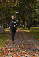 Beautiful female athlete running in park on autumn day.