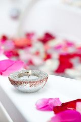 Spa treatment bathtub with floating rose petals and candles