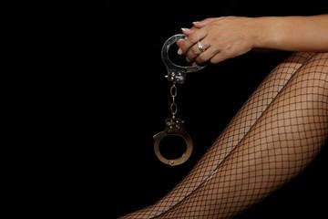 Frauenhand mit Handschellen und Netzstrümpfen