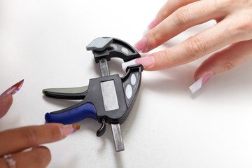 Manicurist make shape to enlarged acrylic nails with clamps