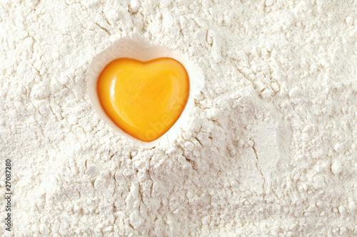 Leinwanddruck Bild love to bake it!  egg  yolk on flour, full frame