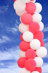 Pink and white balloons on blue sky