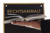Schild aus Metall mit Gesetzbuch und Hand Rechtsanwalt