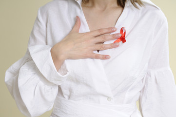 human hand showing red sign for aids