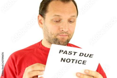 A worried man holding past due notice