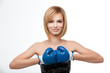 young woman wearing boxing gloves and smiling