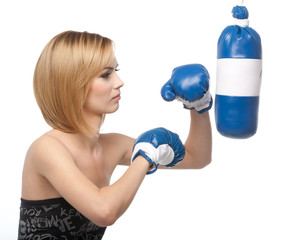 profile of a young woman kicking a punching bag