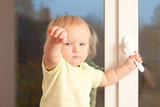Adorable toddler girl stay on the window sill hold knob poster