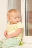 Adorable toddler girl sitting on the window sill look outside poster