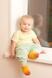 Adorable toddler girl sitting on the window sill poster